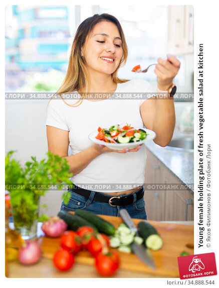 Young female holding plate of fresh vegetable salad at kitchen. Стоковое фото, фотограф Яков Филимонов / Фотобанк Лори
