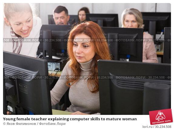 Купить «Young female teacher explaining computer skills to mature woman», фото № 30234508, снято 20 февраля 2019 г. (c) Яков Филимонов / Фотобанк Лори