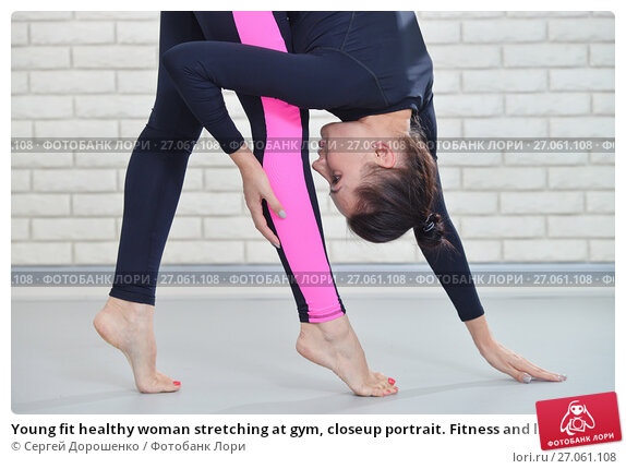 Купить «Young fit healthy woman stretching at gym, closeup portrait. Fitness and lifestyle concept.», фото № 27061108, снято 20 апреля 2018 г. (c) Сергей Дорошенко / Фотобанк Лори