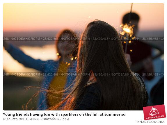 Купить «Young friends having fun with sparklers on the hill at summer su», фото № 28420468, снято 14 мая 2018 г. (c) Константин Шишкин / Фотобанк Лори