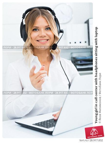 Купить «Young girl in call center with headphones sitting with laptop», фото № 28917832, снято 17 октября 2017 г. (c) Яков Филимонов / Фотобанк Лори