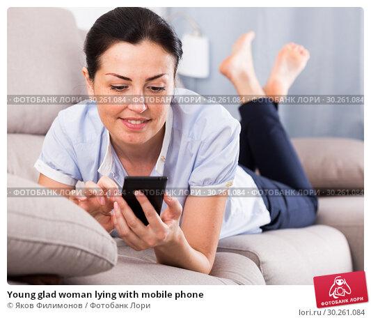 Купить «Young glad woman lying with mobile phone», фото № 30261084, снято 2 июня 2017 г. (c) Яков Филимонов / Фотобанк Лори