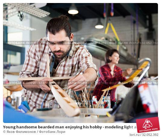Young handsome bearded man enjoying his hobby - modeling light airplanes in aircraft hangar. Стоковое фото, фотограф Яков Филимонов / Фотобанк Лори