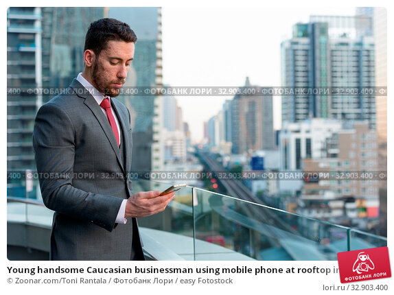 Young handsome Caucasian businessman using mobile phone at rooftop in Bangkok Thailand. Стоковое фото, фотограф Zoonar.com/Toni Rantala / easy Fotostock / Фотобанк Лори