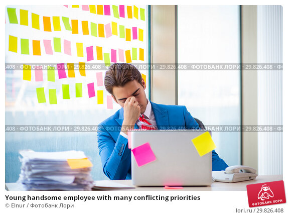 Купить «Young handsome employee with many conflicting priorities», фото № 29826408, снято 15 августа 2018 г. (c) Elnur / Фотобанк Лори