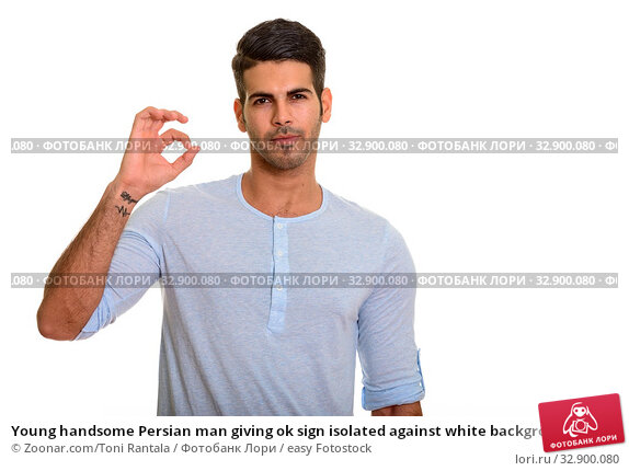 Young handsome Persian man giving ok sign isolated against white background. Стоковое фото, фотограф Zoonar.com/Toni Rantala / easy Fotostock / Фотобанк Лори