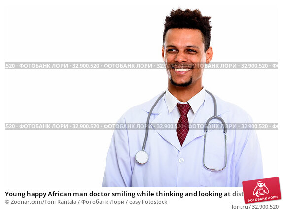 Young happy African man doctor smiling while thinking and looking at distance. Стоковое фото, фотограф Zoonar.com/Toni Rantala / easy Fotostock / Фотобанк Лори