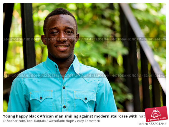 Young happy black African man smiling against modern staircase with nature. Стоковое фото, фотограф Zoonar.com/Toni Rantala / easy Fotostock / Фотобанк Лори