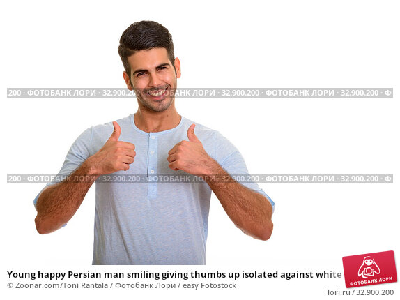 Young happy Persian man smiling giving thumbs up isolated against white background. Стоковое фото, фотограф Zoonar.com/Toni Rantala / easy Fotostock / Фотобанк Лори