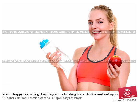 Young happy teenage girl smiling while holding water bottle and red apple ready for gym. Стоковое фото, фотограф Zoonar.com/Toni Rantala / easy Fotostock / Фотобанк Лори