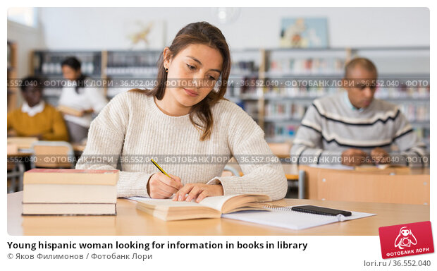 Young hispanic woman looking for information in books in library. Стоковое фото, фотограф Яков Филимонов / Фотобанк Лори