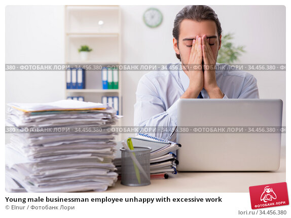 Young male businessman employee unhappy with excessive work. Стоковое фото, фотограф Elnur / Фотобанк Лори