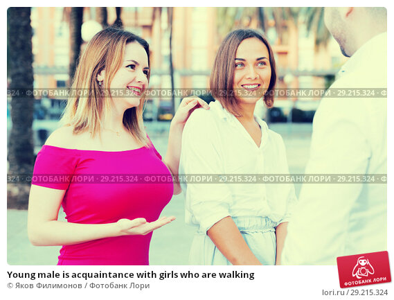 Купить «Young male is acquaintance with girls who are walking», фото № 29215324, снято 18 октября 2017 г. (c) Яков Филимонов / Фотобанк Лори
