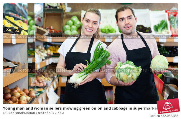 Young man and woman sellers showing green onion and cabbage in supermarket. Стоковое фото, фотограф Яков Филимонов / Фотобанк Лори