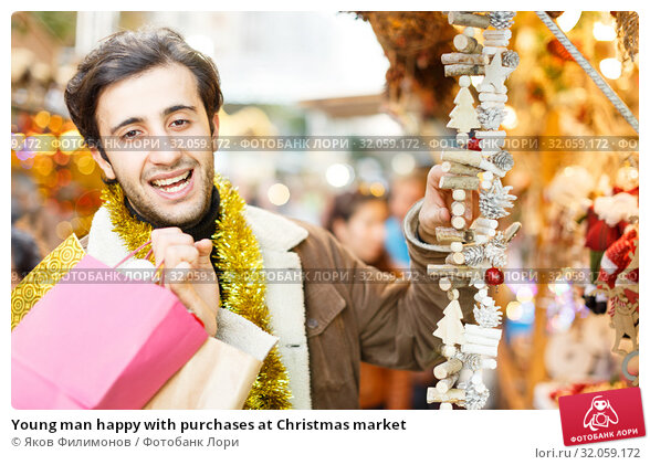 Young man happy with purchases at Christmas market. Стоковое фото, фотограф Яков Филимонов / Фотобанк Лори