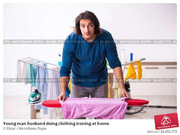 Young man husband doing clothing ironing at home. Стоковое фото, фотограф Elnur / Фотобанк Лори