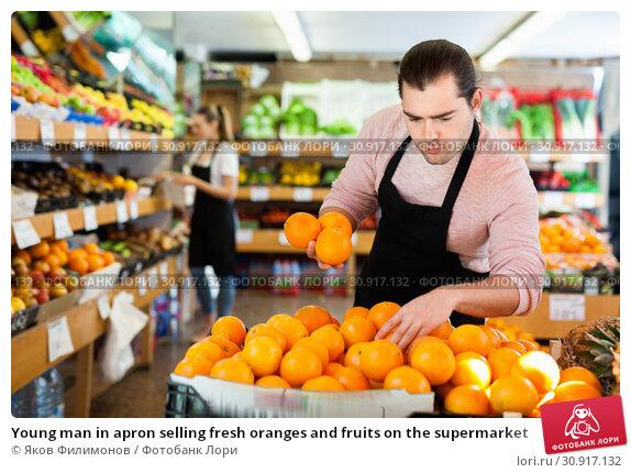 Купить «Young man in apron selling fresh oranges and fruits on the supermarket», фото № 30917132, снято 27 апреля 2019 г. (c) Яков Филимонов / Фотобанк Лори