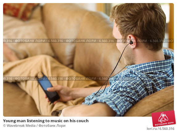 Young man listening to music on his couch. Стоковое фото, агентство Wavebreak Media / Фотобанк Лори