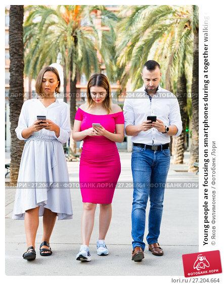 Купить «Young people are focusing on smartphones during a together walking outdoors.», фото № 27204664, снято 18 октября 2017 г. (c) Яков Филимонов / Фотобанк Лори