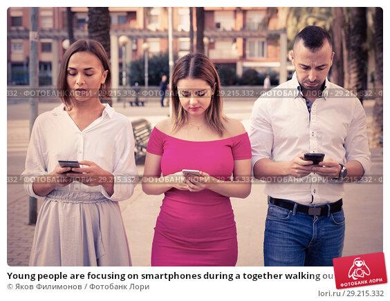 Купить «Young people are focusing on smartphones during a together walking outdoors.», фото № 29215332, снято 18 октября 2017 г. (c) Яков Филимонов / Фотобанк Лори