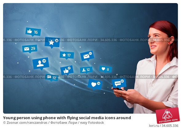 Young person using phone with flying social media icons around. Стоковое фото, фотограф Zoonar.com/ranczandras / easy Fotostock / Фотобанк Лори