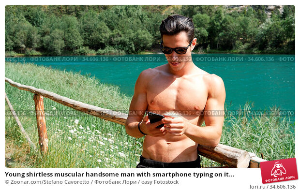 Young shirtless muscular handsome man with smartphone typing on it... Стоковое фото, фотограф Zoonar.com/Stefano Cavoretto / easy Fotostock / Фотобанк Лори