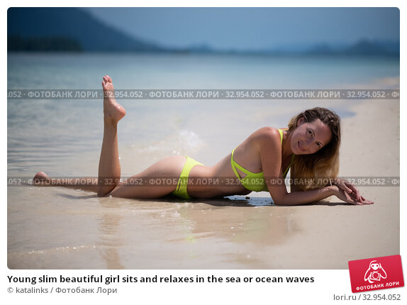 Young slim beautiful girl sits and relaxes in the sea or ocean waves. Стоковое фото, фотограф katalinks / Фотобанк Лори