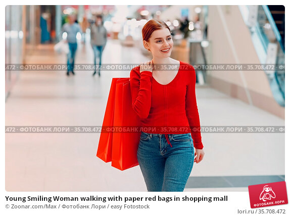 Young Smiling Woman walking with paper red bags in shopping mall. Стоковое фото, фотограф Zoonar.com/Max / easy Fotostock / Фотобанк Лори