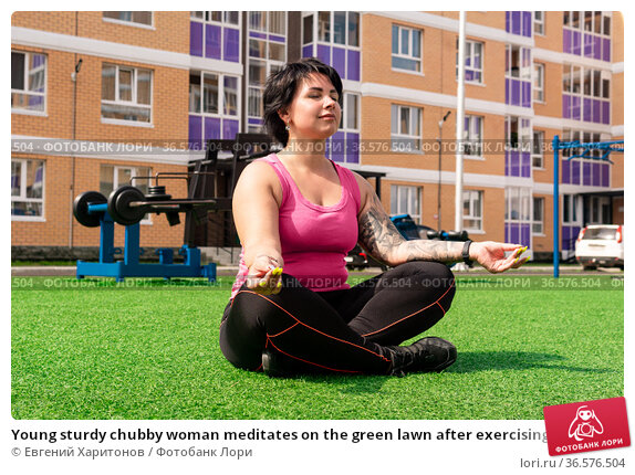 Young sturdy chubby woman meditates on the green lawn after exercising in the courtyard of a city house against the background of street gym equipment. Стоковое фото, фотограф Евгений Харитонов / Фотобанк Лори