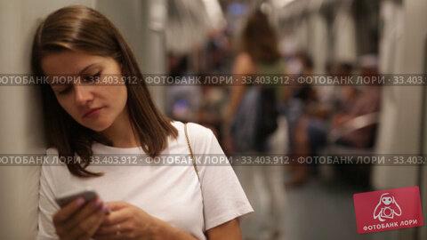 Купить «Young woman browsing and typing messages on phone in subway car», видеоролик № 33403912, снято 19 сентября 2019 г. (c) Яков Филимонов / Фотобанк Лори