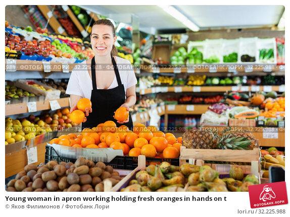 Купить «Young woman in apron working holding fresh oranges in hands on t», фото № 32225988, снято 27 апреля 2019 г. (c) Яков Филимонов / Фотобанк Лори