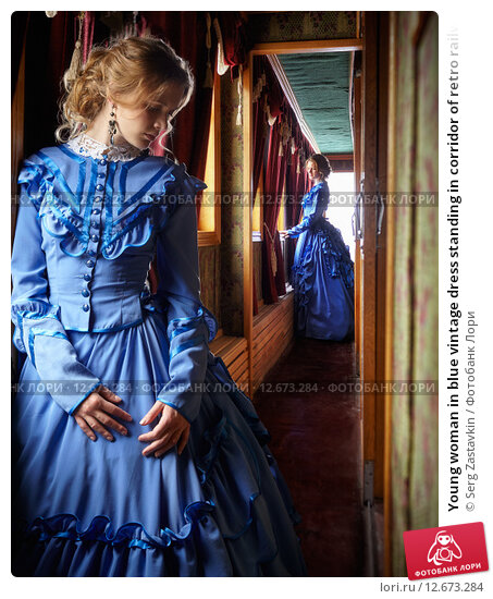 Young woman in blue vintage dress standing in corridor of retro railway vehicle, фото № 12673284, снято 12 июля 2015 г. (c) Serg Zastavkin / Фотобанк Лори