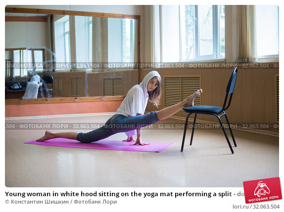 Young woman in white hood sitting on the yoga mat performing a split - doing leg stretching exercises using a chair - dance studio. Стоковое фото, фотограф Константин Шишкин / Фотобанк Лори