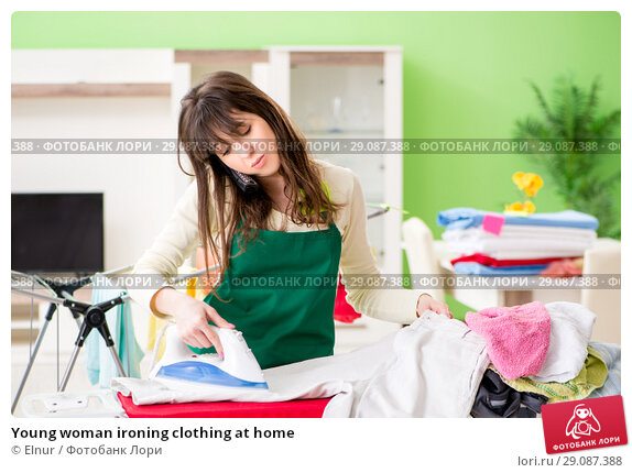 Купить «Young woman ironing clothing at home», фото № 29087388, снято 29 мая 2018 г. (c) Elnur / Фотобанк Лори