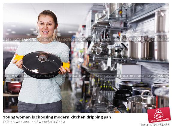 Young woman is choosing modern kitchen dripping pan. Стоковое фото, фотограф Яков Филимонов / Фотобанк Лори