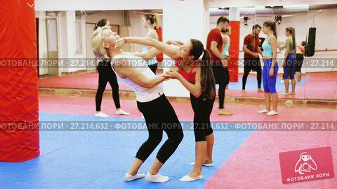 Купить «Young woman is doing self-defence moves with coach in sporty gym.», видеоролик № 27214632, снято 22 октября 2017 г. (c) Яков Филимонов / Фотобанк Лори