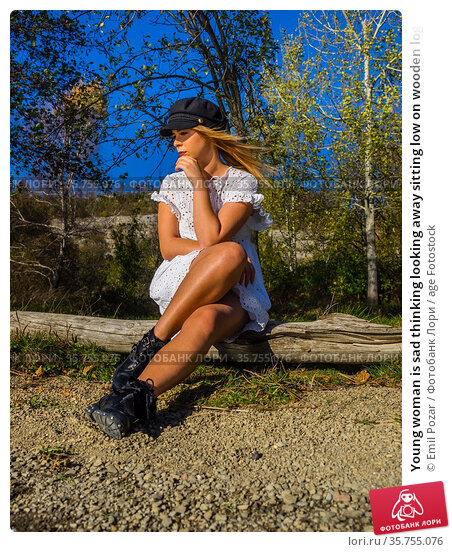 Young woman is sad thinking looking away sitting low on wooden log. Стоковое фото, фотограф Emil Pozar / age Fotostock / Фотобанк Лори