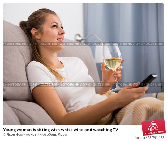 Young woman is sitting with white wine and watching TV. Стоковое фото, фотограф Яков Филимонов / Фотобанк Лори