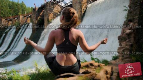 Young woman on vacation doing yoga near the water dam - meditating. Стоковое видео, видеограф Константин Шишкин / Фотобанк Лори