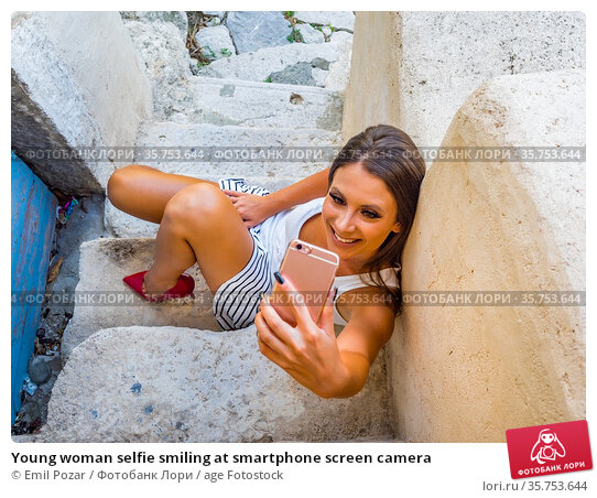 Young woman selfie smiling at smartphone screen camera. Стоковое фото, фотограф Emil Pozar / age Fotostock / Фотобанк Лори