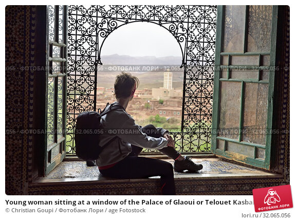 Young woman sitting at a window of the Palace of Glaoui or Telouet Kasbah, on the outskirts of the village of Telouet, Ouarzazate Province, region of Draa-Tafilalet, Morocco, North West Africa. (2019 год). Редакционное фото, фотограф Christian Goupi / age Fotostock / Фотобанк Лори