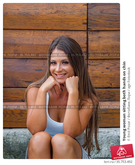 Young woman sitting both hands on chin. Стоковое фото, фотограф Emil Pozar / age Fotostock / Фотобанк Лори