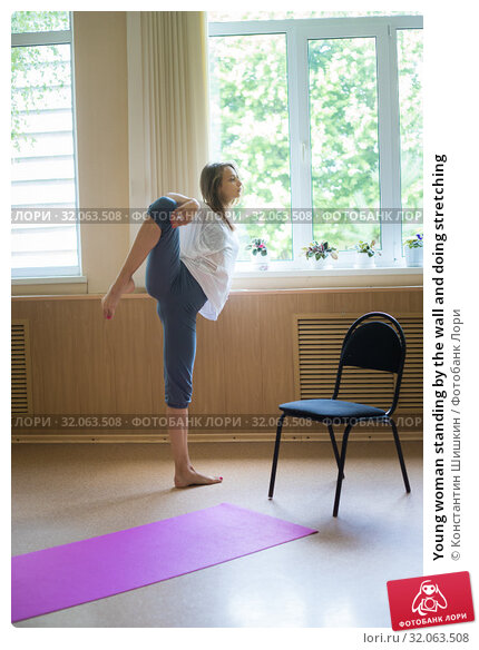 Young woman standing by the wall and doing stretching. Стоковое фото, фотограф Константин Шишкин / Фотобанк Лори