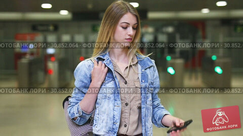 Купить «Young woman traveler looking at itinerary map at metro station», видеоролик № 30852064, снято 25 апреля 2019 г. (c) Яков Филимонов / Фотобанк Лори
