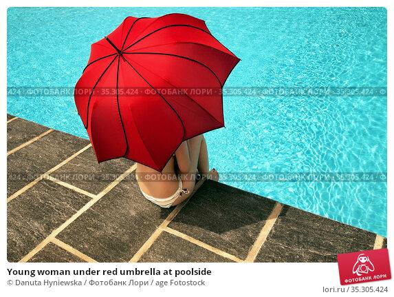 Young woman under red umbrella at poolside. Стоковое фото, фотограф Danuta Hyniewska / age Fotostock / Фотобанк Лори