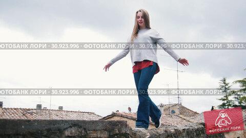 Купить «Young woman walks on the roof keeping the balance with her hands», видеоролик № 30923996, снято 17 июня 2019 г. (c) Константин Шишкин / Фотобанк Лори