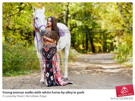 Купить «Young woman walks with white horse by alley in park», фото № 25836516, снято 20 сентября 2015 г. (c) Losevsky Pavel / Фотобанк Лори