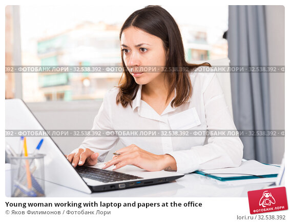 Купить «Young woman working with laptop and papers at the office», фото № 32538392, снято 1 мая 2018 г. (c) Яков Филимонов / Фотобанк Лори