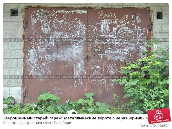 Купить «Заброшенный старый гараж. Металлические ворота с неразборчивыми надписями и рисунками», фото № 34099524, снято 23 августа 2019 г. (c) александр афанасьев / Фотобанк Лори
