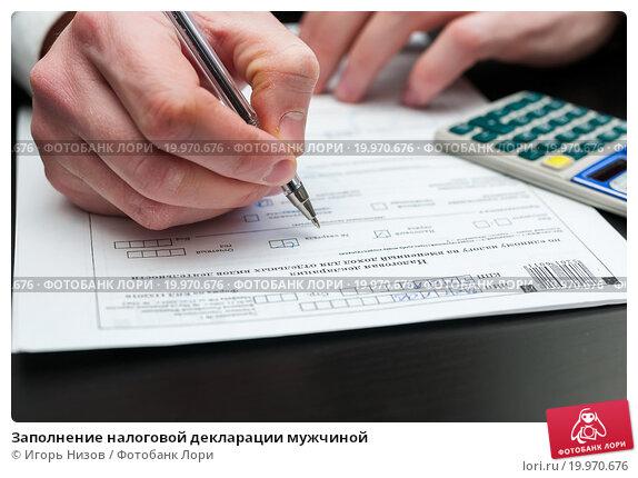 Заполнение налоговой декларации мужчиной, эксклюзивное фото № 19970676, снято 10 января 2016 г. (c) Игорь Низов / Фотобанк Лори
